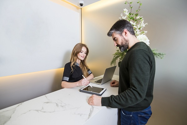Receptionist writing on a tablet with a customer