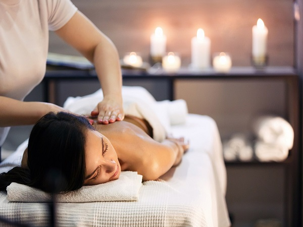 A person receiving a massage in a candle lit room